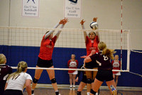 Brianna Miller and Jada Cattau go up for a block on a Mackenzie Foxhoven spike attempt